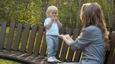 anyaság : Toddler standing on the bench and eating cookies