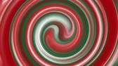 Christmas spiral effect background in red and green colors. Realistic 3d holiday spin loop from top view angle. Abstract loopable xmas animation footage.