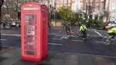 Cyclists in a cycle lane go past a British phone box Stock Footage