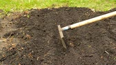 ültetés : Preparation of beds for planting vegetables, loosening the soil with a rake. Preparation of soil in early spring for a good harvest