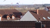 kikötve : kites soar over the roofs of houses