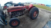 arando : Old antique Massey Ferguson 135 tractor with a gas engine sits parked on a farm yard. Vídeos