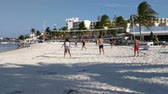 Group of young people play beach volleyball in the hotel zone. Vídeos