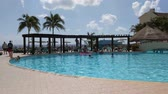 Tropical Paradise holiday makers sun bathe and swim in a luxury hotel pool.