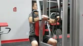 Young fit male model exercising reverse fly shoulder delts machine.