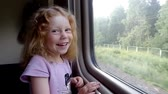 Beautiful little girl laughing in front of the train window while travelling raylway