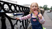 Charm little girl walking along the river embankment sucking lollipop Stock Footage