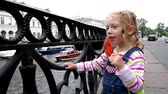 Charm little girl at river embankment sucking lollipop and looking at boats Stock Footage