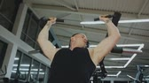 slider bar : A muscular man in a black T-shirt is training on a fitness machine in a fitness club.