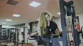 uzatma : Very beautiful female trainer trains on a fitness machine in a fitness club Stok Video