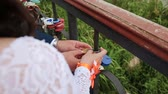 toka : Groom hanging wedding padlock on the pipe near a variety of padlocks. Wedding colorful locks hanging on the pipes of a pedestrian bridge the background a river. Close-up