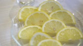 цитрон : Sliced lemons on a glass plate close up.