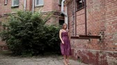 demonstrar : Very beautiful girl posing in the old courtyard of brick houses. Stock Footage
