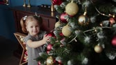 suéter : Very beautiful little girl stands near the New Year tree and touches toys.