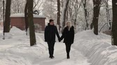 casal : Beautiful young couple walking in the park holding hands.