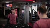 Handsome sporty man training dumbbell biceps in the gym.
