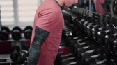 bicepsz : Handsome sporty man training dumbbell biceps in the gym.