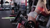 atleta : Very beautiful and sexy fitness model trains back thigh on a gym machine in the gym. Vídeos