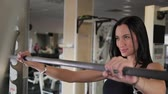 činka : Beautiful athletic young girl crouches on the shoulders in the gym. Dostupné videozáznamy
