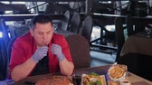 bites lip : Fat man is ugly eating a big burger. Stock Footage