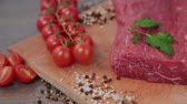 biber tanesi : raw beef on a wooden background with spices and tomatoes.