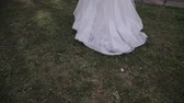 gown : Beautiful young bride walks on the grass with a train of wedding dress.