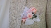 смокинг : Boutonniere in the pocket of the jacket of the groom in his wedding day. Clip. Rose in his jacket pocket.