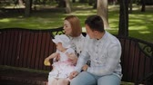 ławka : Happy young family with his son resting in the Park in the summer on a bench. A beautiful woman with her husband and a child sitting on a bench in the background of the urban landscape Wideo