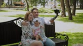 ławka : Happy family with a child take a selfie on a bench in the park.
