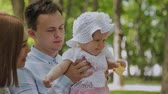 książka : Happy young family with his son resting in the Park in the summer on a bench. A beautiful woman with her husband and a child sitting on a bench in the background of the urban landscape Wideo