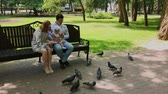 moederdag : Family feeds pigeons at the park bench. Stockvideo