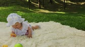 A very small and beautiful girl playing on the bedspread in the park.