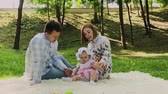flower bed : Happy family mom and dad playing with baby on bedspread. Stock Footage