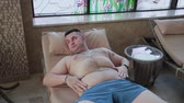 точка зрения : Overweight man lying on a lounger by the indoor pool. Стоковые видеозаписи