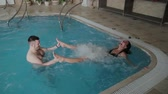 srdce : Young man and woman joking and smiling in the pool. Dostupné videozáznamy