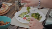 brunch'ı : A young man is having lunch with a salad with vegetables in a restaurant on the open terrace. Healthy food. Stok Video