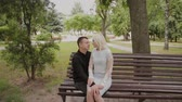 female cell : Happy couple in love sitting on a bench in a city park.