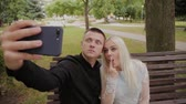 falésias : Happy couple in love sitting on a bench in the city park and making selfie on the phone. Vídeos