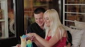 coquetel : Beautiful girl and guy with fresh cocktails in the evening cafe. Stock Footage