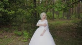 wedding bouquet : Beautiful blonde bride in the forest strokes herself