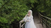 everlasting : Beautiful blonde bride on a bridge near the railing in the forest.