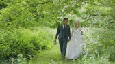buquê : Very beautiful bride and groom hold hands and hug in the forest. Stock Footage