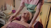 nemlendirici : Professional cosmetologist makes massage to an elderly woman. Cosmetological innovations