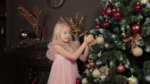 A ten-year-old girl near the New Year tree holds a New Year s toy in her hands. New Year 2020. 動画素材