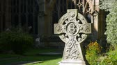 celta : Still shot of a sunlit celtic cross gravestone decorated with leaves and  flowers. Vídeos