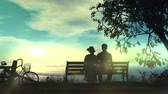 Couple on a bench watching the ocean Stock Footage