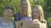 относительный : Grandmother, her daughter and grand daughter taking a selfie on a smartphone in the garden Стоковые видеозаписи