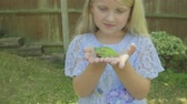 kurbağa : Pre teen caucasian girl holding a white lipped tree frog in her hands Stok Video