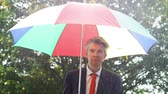 adversidade : Caucasian businessman sheltering under a colourful umbrella in the torrential rain Vídeos