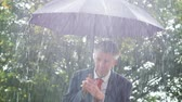 adversidade : Caucasian businessman sheltering underneath an umbrella in the torrential rain